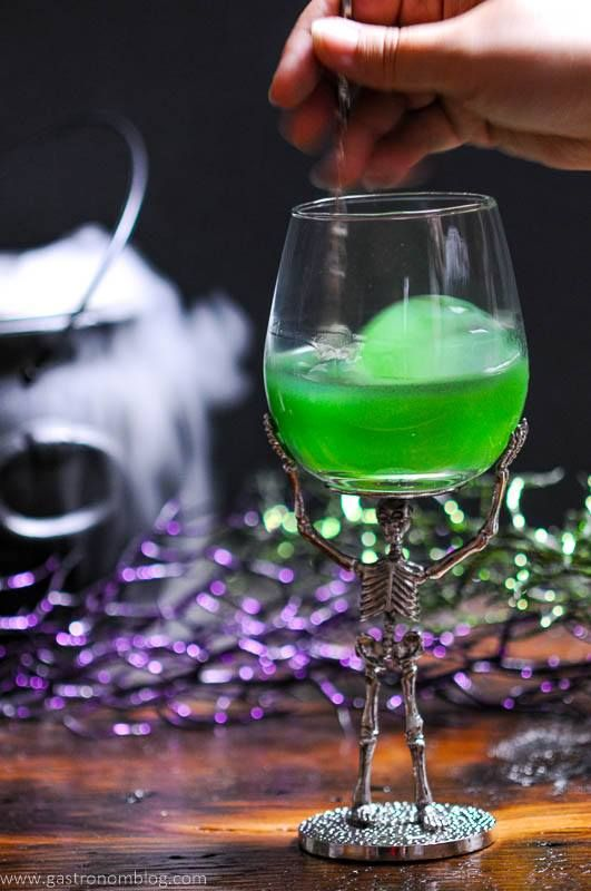 A green Halloween cocktail called the Grindelwald's Goblet is presented with a large circular ice cube in a skeleton based wine glass.