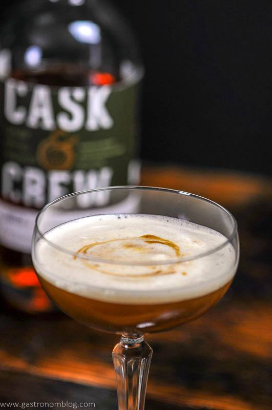 A close up of the Holiday Ginger Flip Cocktail and a bottle of Cask and Crew Ginger Spice Whiskey.
