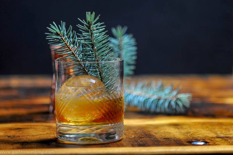 A hand cut crystal rocks glass filled with a Pine Old Fashioned with a clear sphere of ice and a pine branch garnish on a bar top.