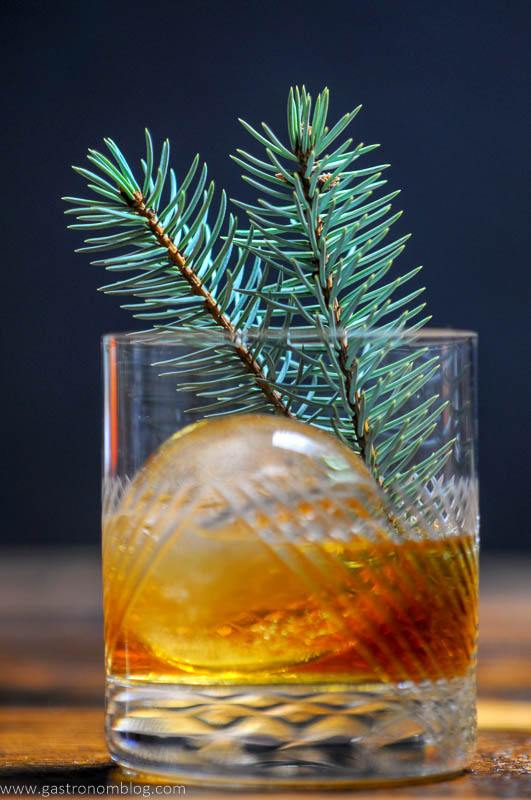 A close up shot of a Pine Old Fashioned Cocktail in a crystal rocks glass on a wooden bar top.