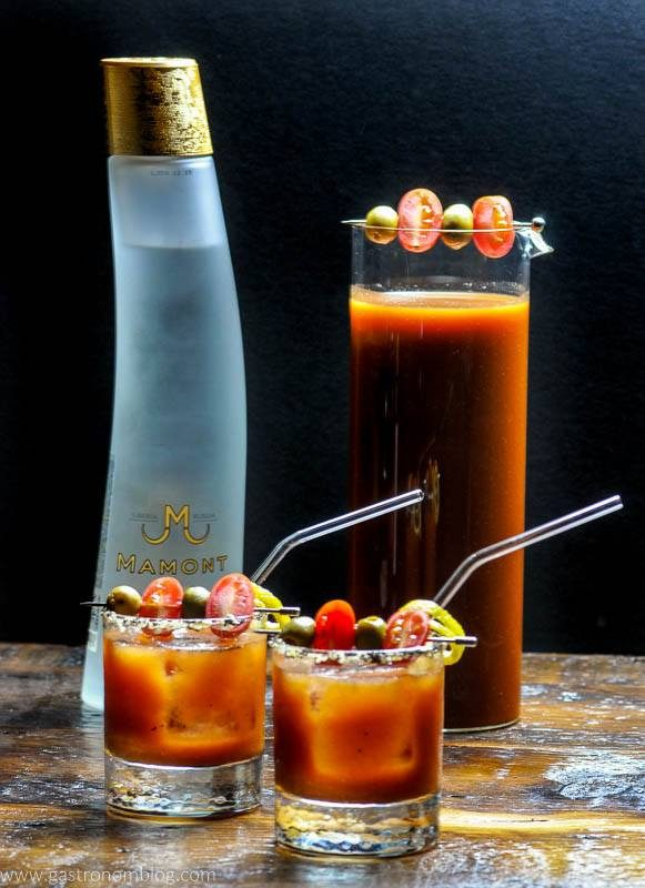 A pair of rocks glasses and a glass pitcher filled with a Bloody Mary cocktails sits on a wooden bar top with a bottle of Mamont Vodka alongside to celebrate National Bloody Mary Day.