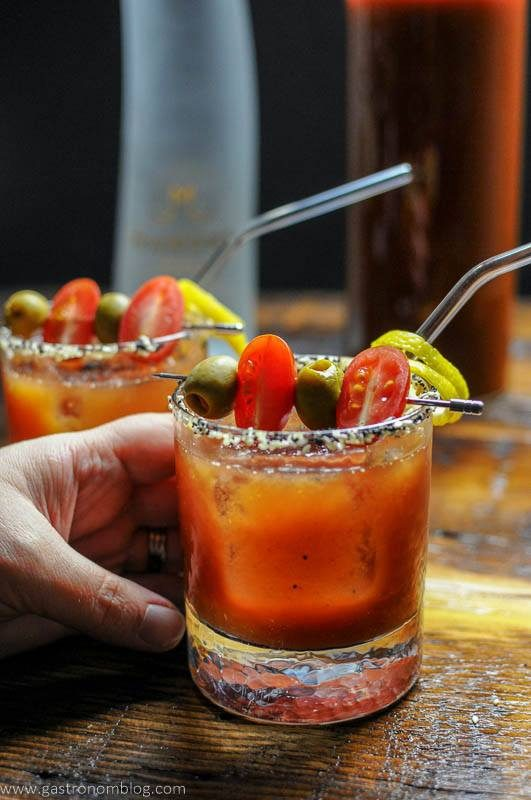 A hand grasps a rocks glass filled with a Bloody Mary Cocktail topped with olives and cherry tomatoes as a garnish.