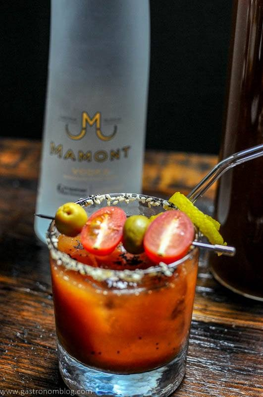 A rocks glass filled with a Bloody Mary cocktail sits on a wooden bar top with a bottle of Mamont Vodka alongside to celebrate National Bloody Mary Day.
