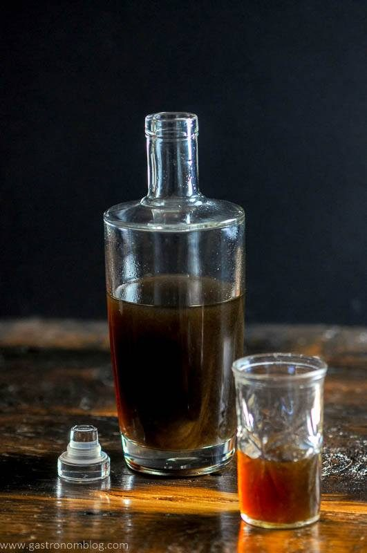 A bottle full of homemade banana liqueur sits on a wooden bar top next to a small shot glass with banana liqueur in it.