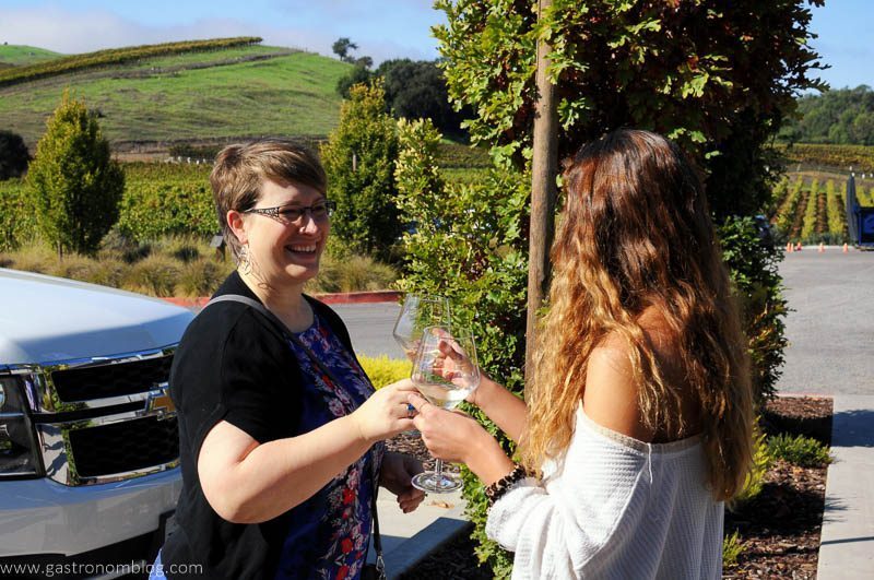 A hostess meets guests at the parking lot with a glass of their white wine.