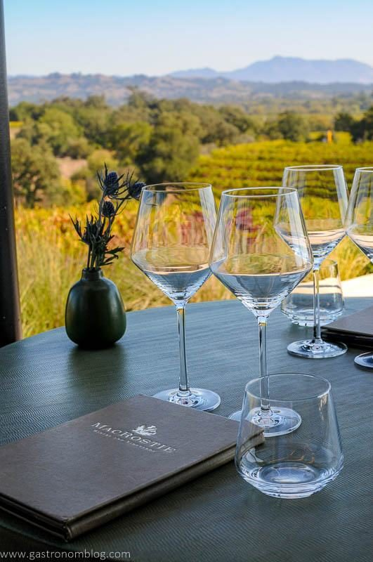Wine glasses and a tasting menu sit at a table for tasting at MacRostie Vineyards.