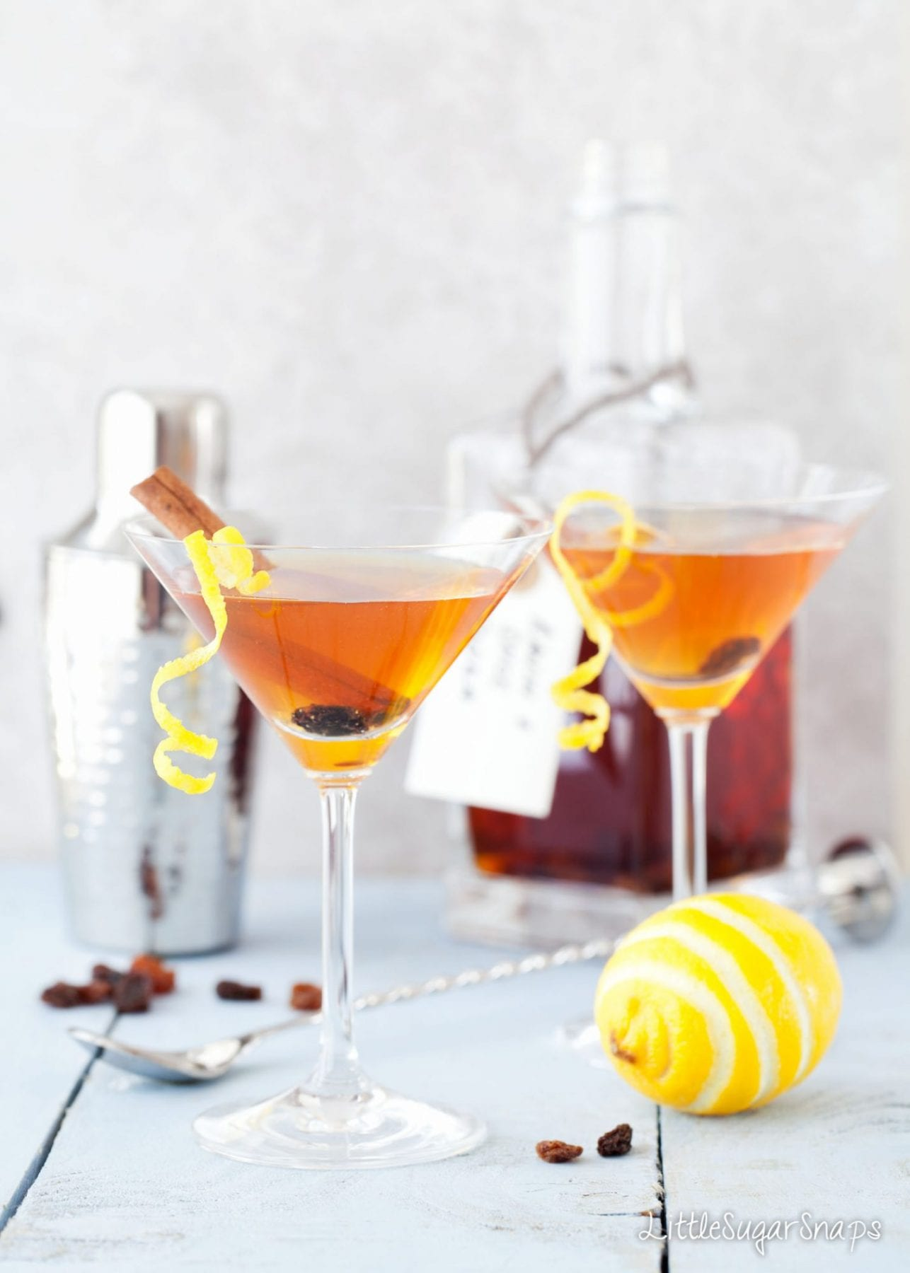 Gold cocktails in martini glasses, liqueur in bottle, lemon and spices