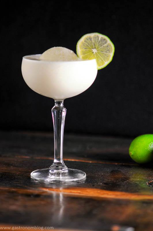 White Chocolate Martini in a coupe glass with ice ball, lime wheel, limes and bottle in background