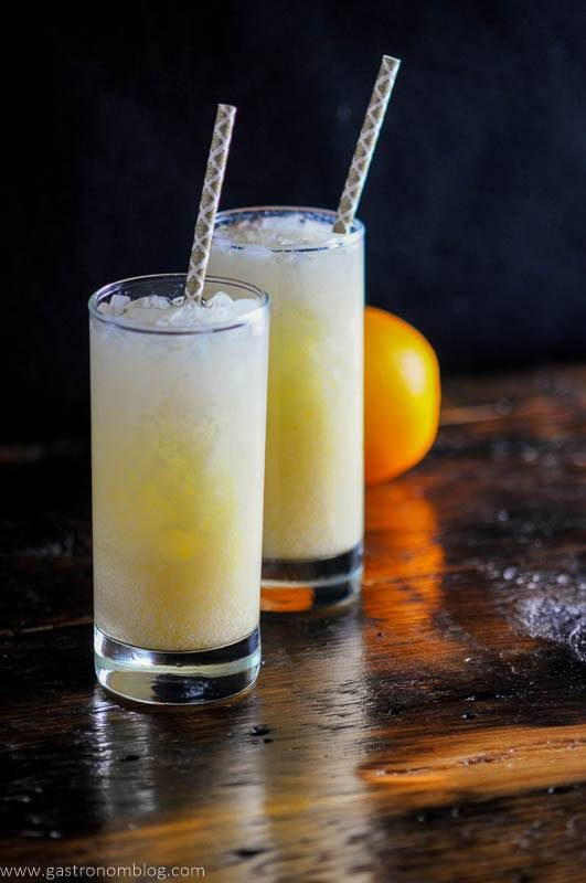 orange dreamsicle cocktail with straws and an orange on wooden board