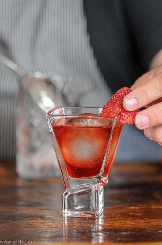 red cocktail in glass, strawberry being placed by a hand
