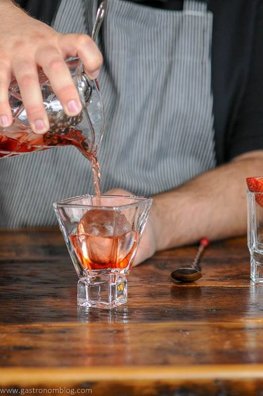 strawberry cocktail being poured into glass