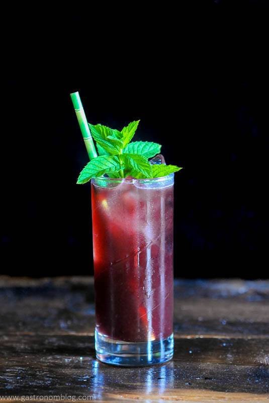 Red cocktail with mint and straw