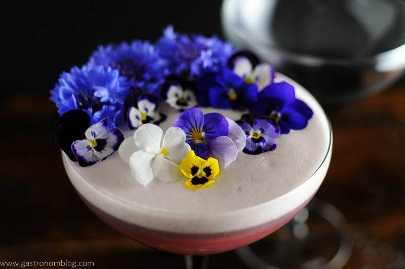 Egg white foam topped cocktail with edible flowers