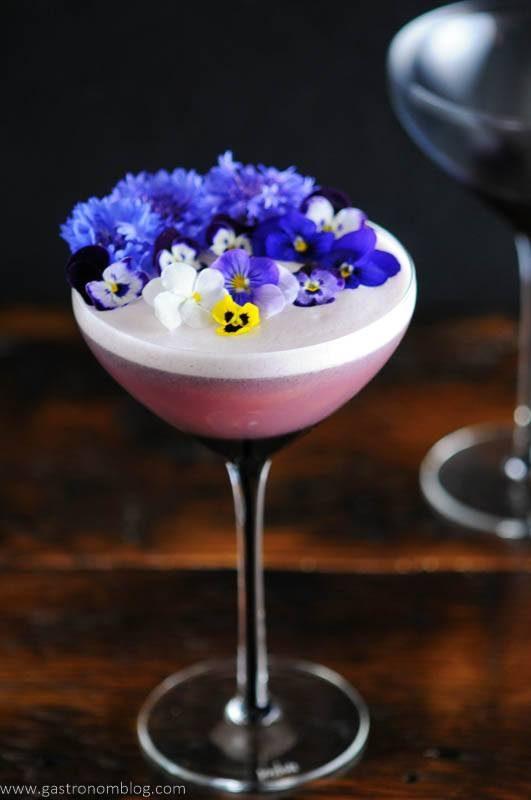 Edible flowers on egg foam in purple coupe