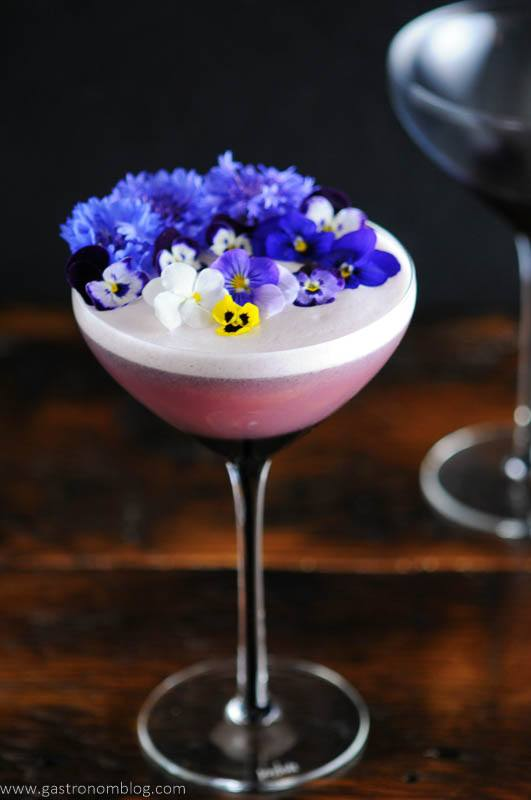 Edible flowers on egg foam in purple coupe