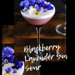 Purple cocktail in purple coupe with edible flowers