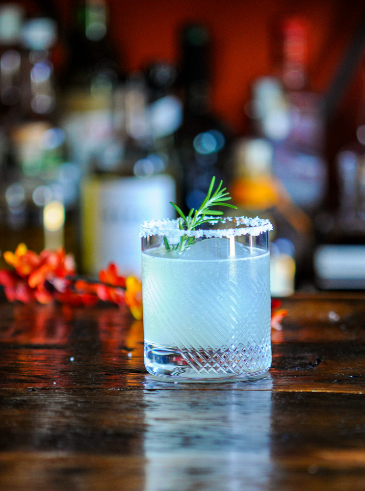 Cocktail in rocks glass wtih rosemary sprig and salt rim