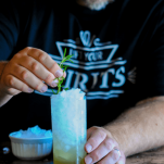Man placing straw in highball drink