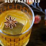 Whiskey cocktail in glass with star anise on top of ice, top shot