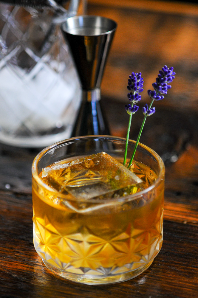 whiskey cocktail in rocks glass with lavender sprigs