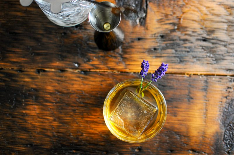 Top shot of whiskey cocktail, clear ice and lavender sprigs