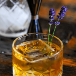 Whiskey cocktail with clear ice in rocks glass, lavender sprigs