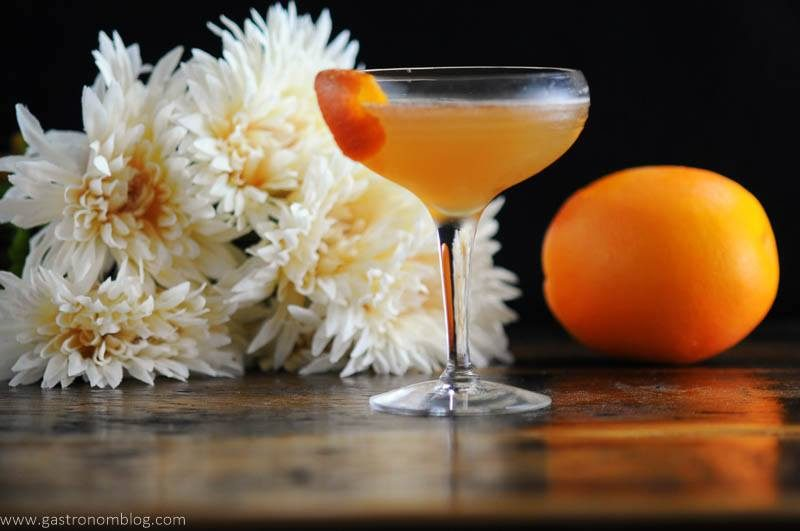 orange cocktail in coupe, white flowers behind