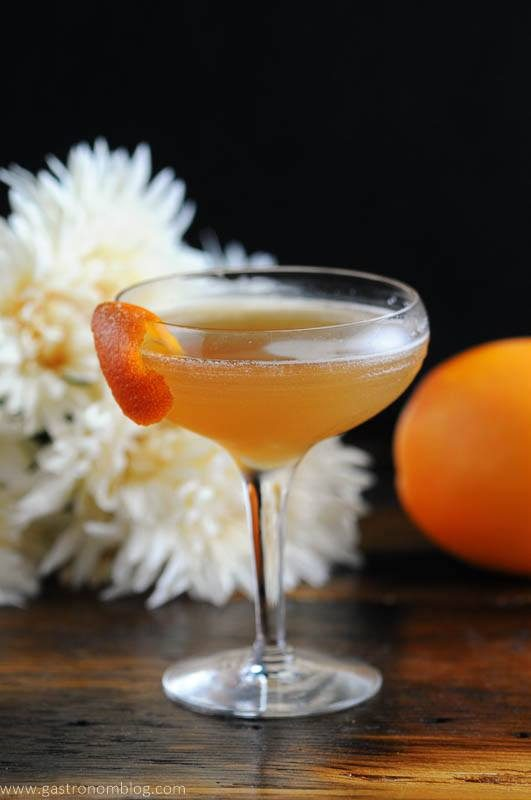 Cocktail in coupe with orange peel, white flowers behind