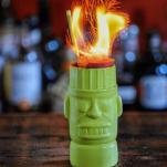 Green Tiki mug with zombie cocktail and flames