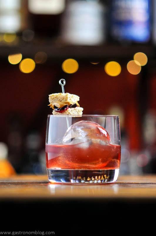 Cocktail in rocks glass, sandwich garnish