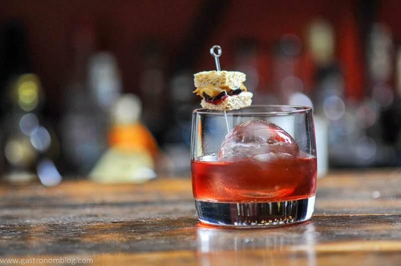 cocktail with tiny sandwich garnish