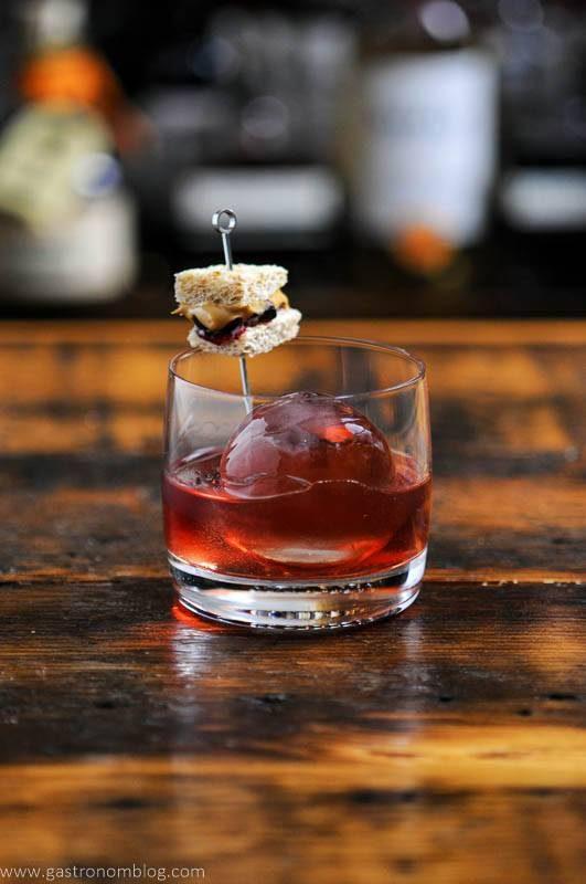 Pink cocktail with sandwich garnish on pick