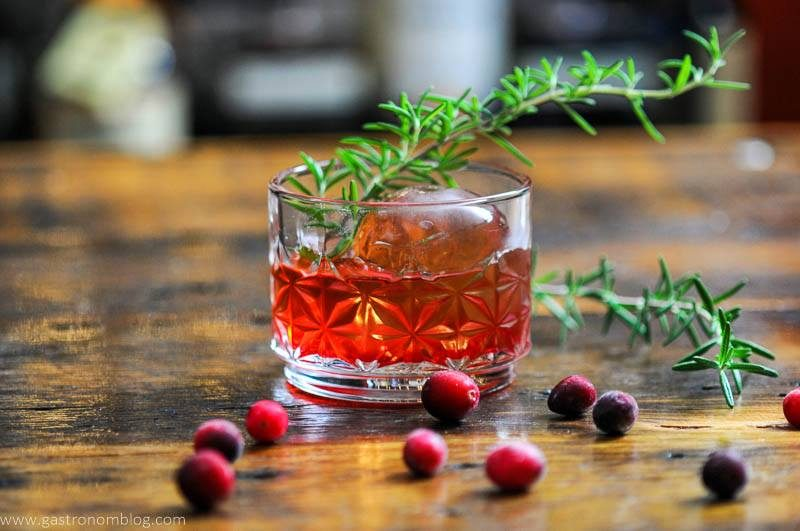 Red cocktail in rocks glass, rosemary sprig