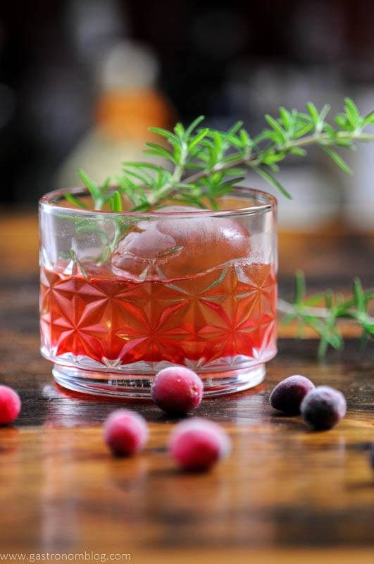 Cranberries around red cocktail in glass with rosemary