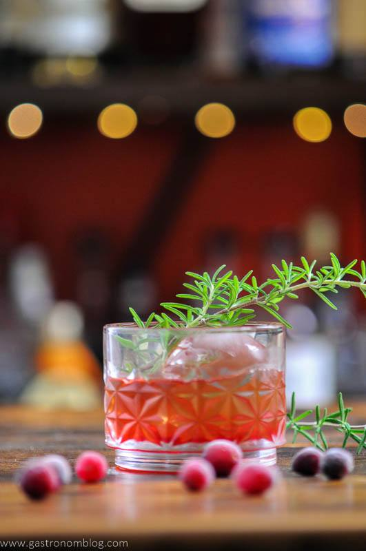 Red Holiday cocktail in glass, with rosemary and cranberries