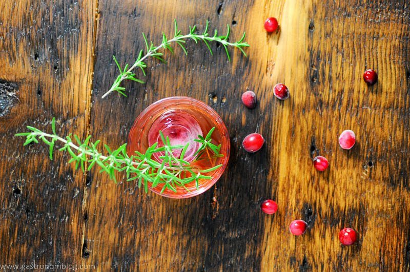 Top shot of red cocktail with cranberries and rosemary