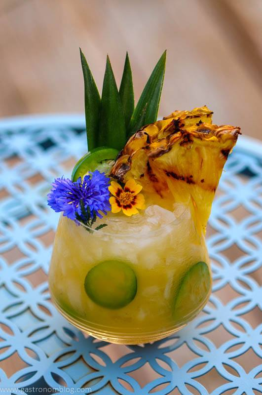 Yellow cocktail with pineapple slice and edible flowers on blue table