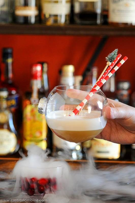 Christmas cocktail being held , dry ice, cranberries and red and white straws