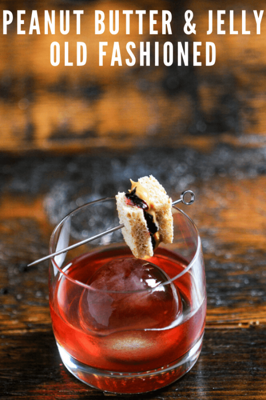 Pink cocktail in rocks glass with tiny pb&j sandwich