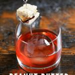 Cocktail in rocks glass with tiny sandwich