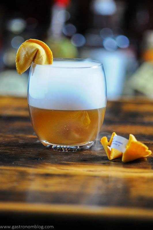 Tan cocktail in glass with dry ice smog on top, fortune cookies
