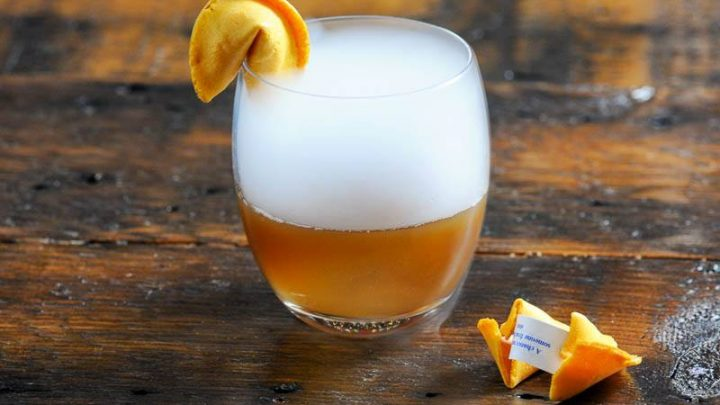 Tan cocktail with dry ice and fortune cookie
