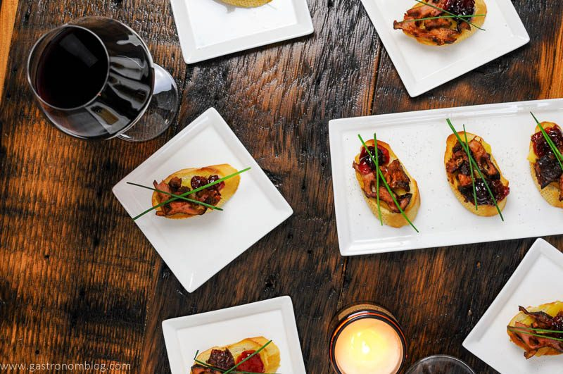 Pork Crostini on white plates, wine in glasses