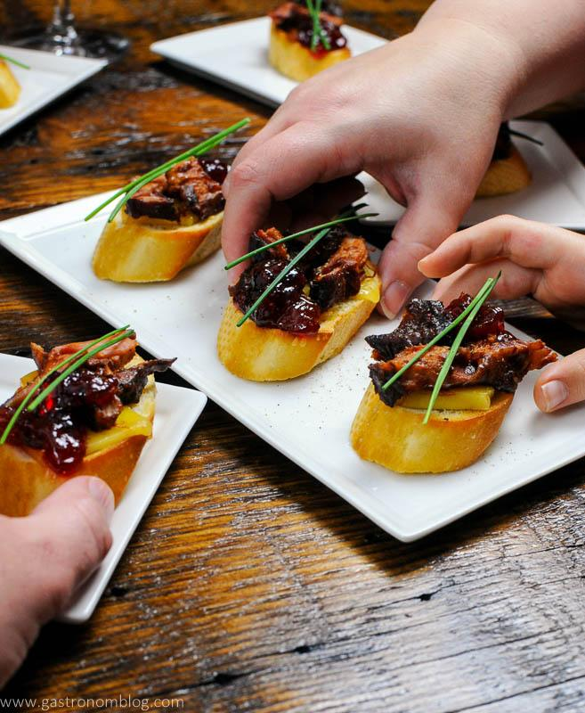 Pork Crostini on white plates, hands picking up