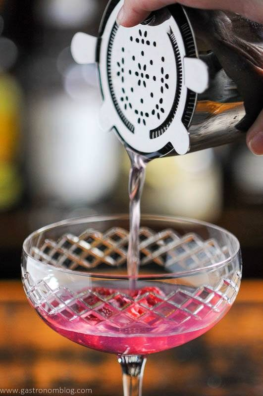 Pink cocktail being poured into coupe