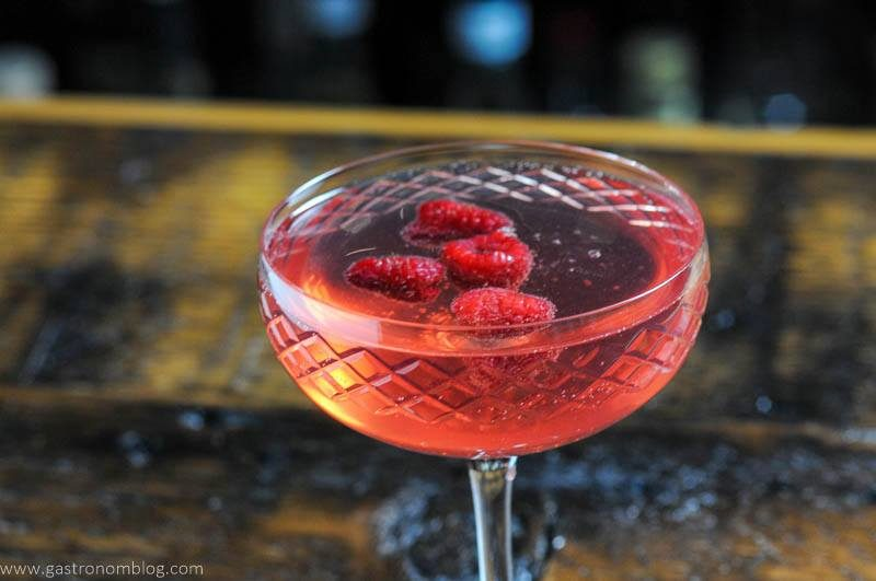 pink cocktail in coupe with raspberries