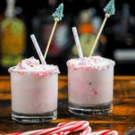 Pink cocktails in glasses with straws and candy canes