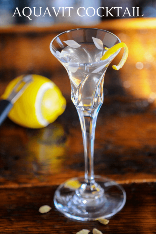 Clear cocktail in glass with lemon peel. Lemon in back with channel knife.