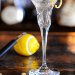 Clear cocktail in tall glass with lemon peel
