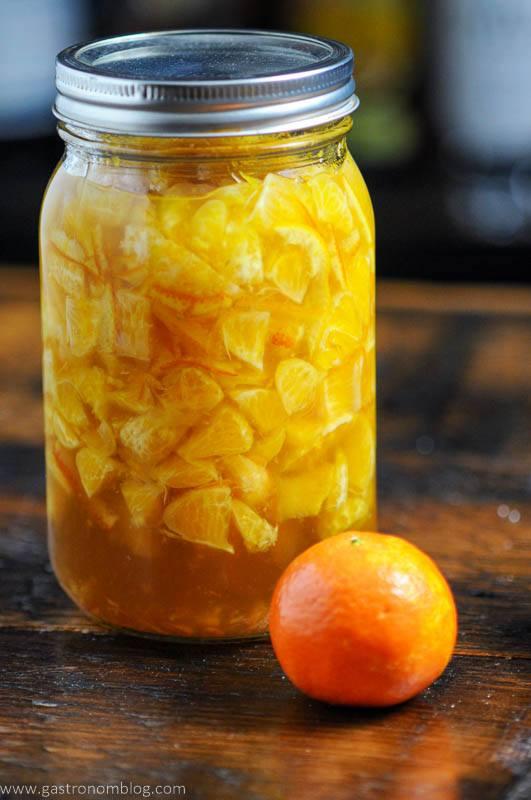 Clementine Shrub, or drinking vinegar, orange liquid in mason jar with an orange on wooden surface
